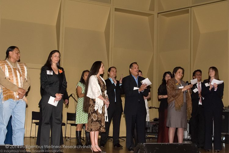 Photo: IWRI Faculty on stage making a vow to do work that supports Indigenous communities